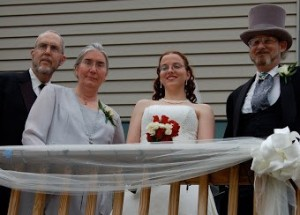 Pictured with my parents at my wedding, step dad and mom to the left, dad to the right, me in the middle holding white and red roses.