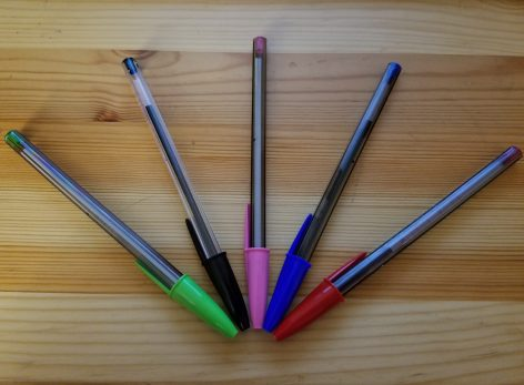 5 Bic pens fanned out. Green, black, pink, blue, and red.