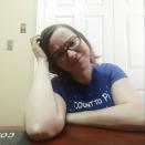 Morgan, in a blue shirt, scratching her head
