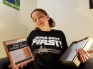 """Morgan in a """"Burr Shot First"""" shirt, holding a book on """"The Guide To Literary Agents"""" and the print-out of her latest draft shrugging and wondering if she should query again."""