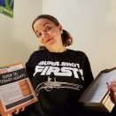 "Morgan in a ""Burr Shot First"" shirt, holding a book on ""The Guide To Literary Agents"" and the print-out of her latest draft shrugging and wondering if she should query again."