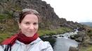 Morgan smiling at the camera with the river at Thingvellar behind her