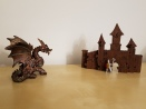 A copper dragon model faces down a tiny plastic knight, in front of a 3d wooden castle puzzle