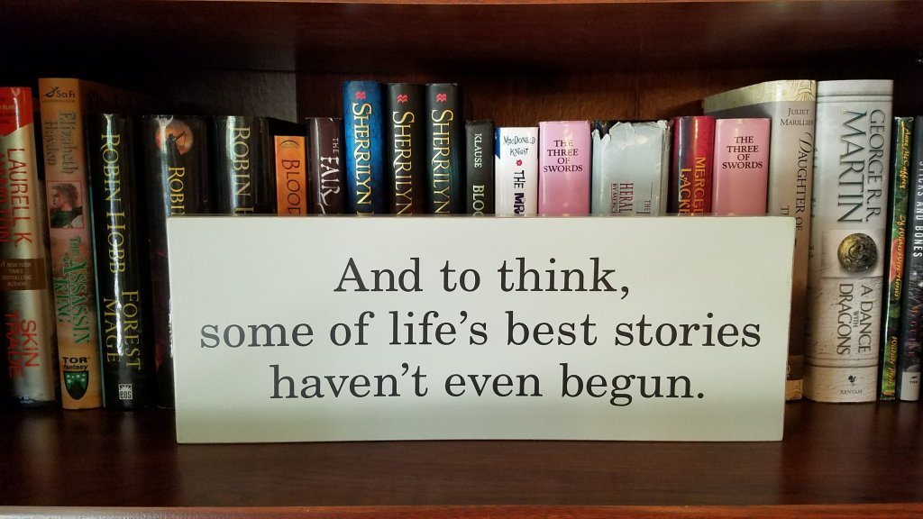 Quote on a grey board on a brown shelf with books behind it.