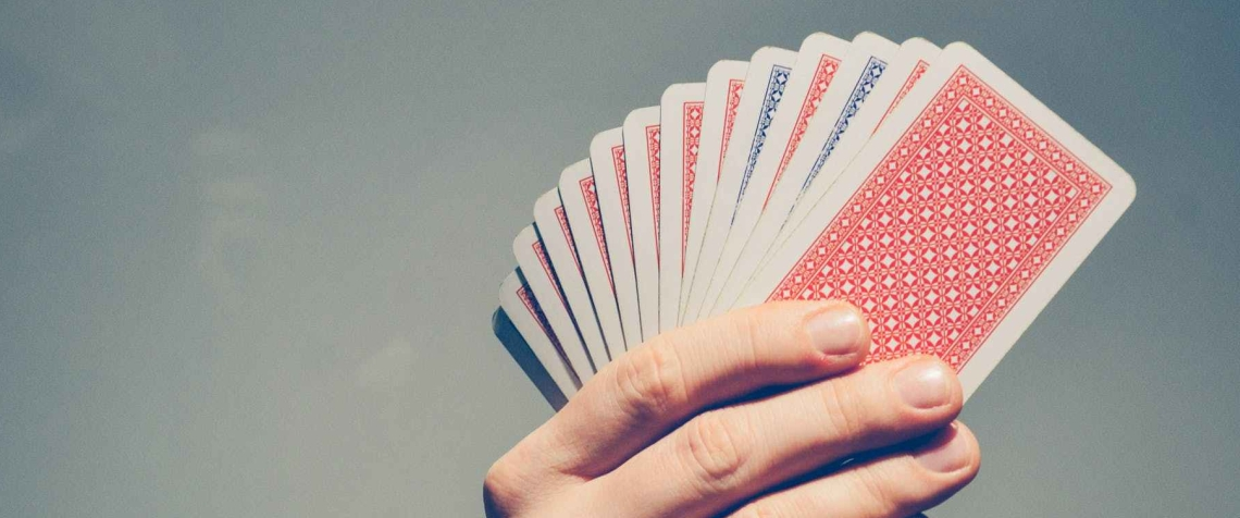 A hand holding a deck of cards, fanned out, facing away from the camera.