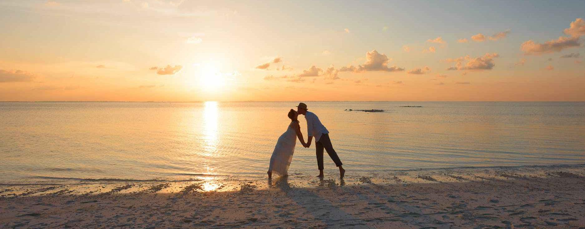 A couple, kissing on a sandy beach at sunset (sunrise?)