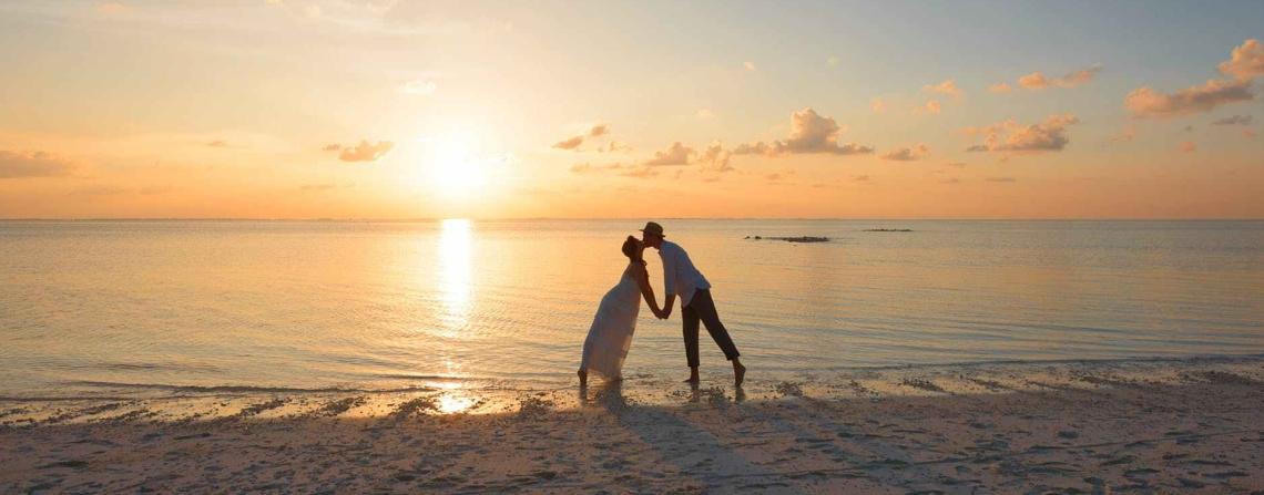 A couple, kissing on a sandy beach at sunset (sunrise?)