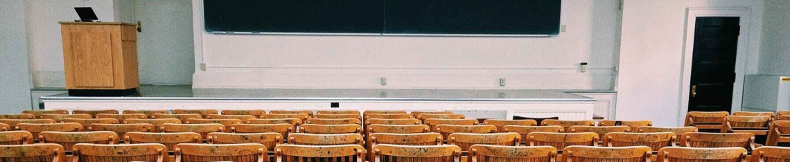 An empty classroom looks at a white board and podium.