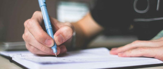 Person holding a blue ballpoint pen writing.