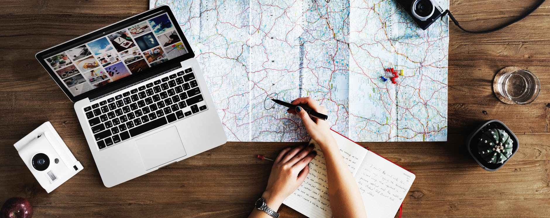 A laptop, a map, a notebook, and a pen held over a spot on the map.