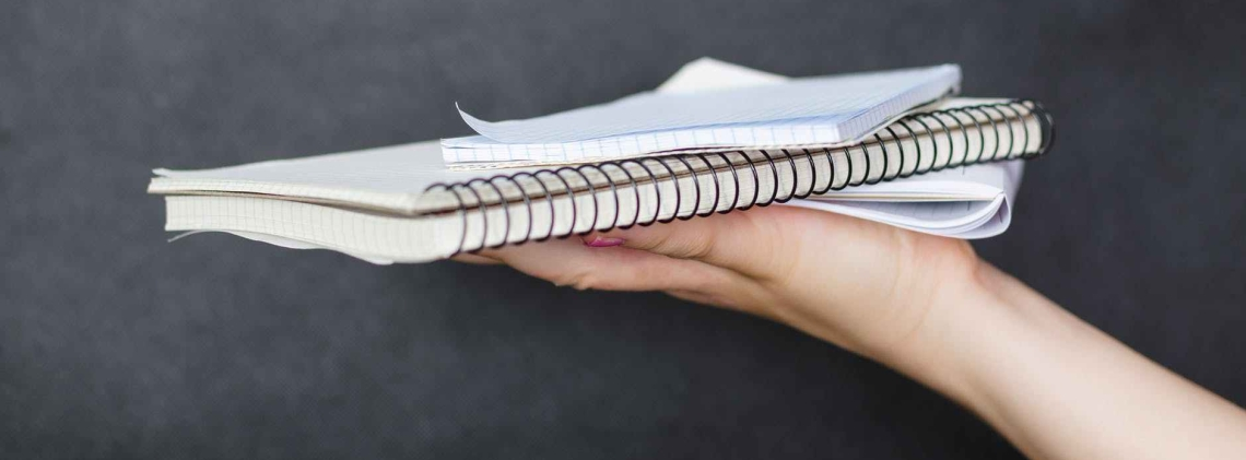 A hand balances 3 notebooks on the palm.
