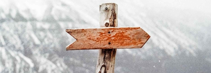 Wood signpost, with worn red arrow pointing right. Greyed out mountains faintly behind it.