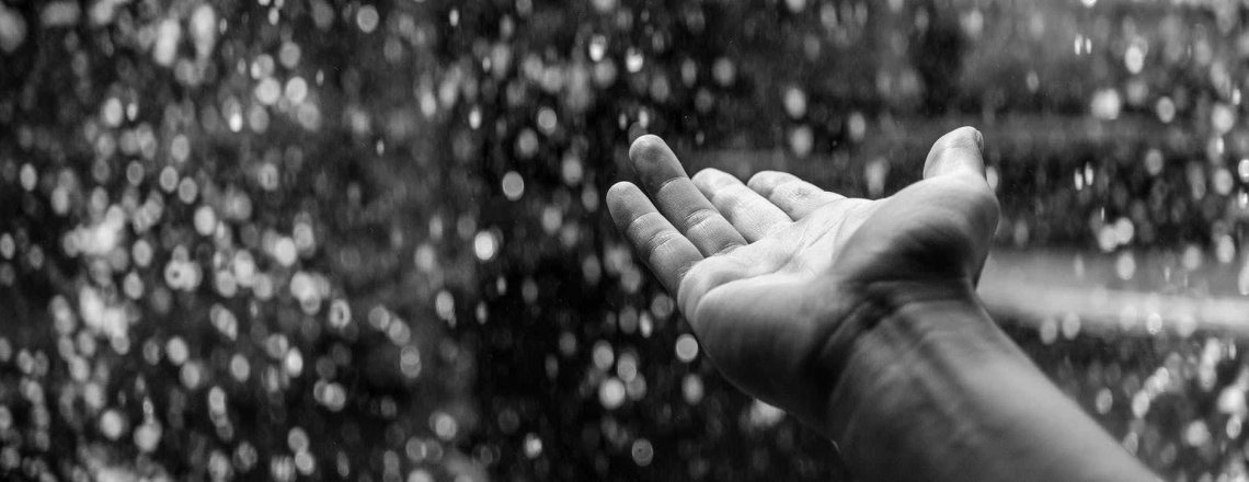 A hand reaching out to feel the falling rain - in black and white/greyscale.