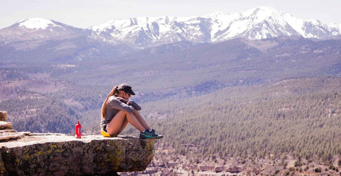 Girl, hugging her knees, sitting at the edge of a cliff with mountains in the background.