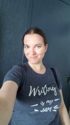 "Morgan, hair pulled back, in a blue t-shirt with white letters: ""Writing is my JAM!"""