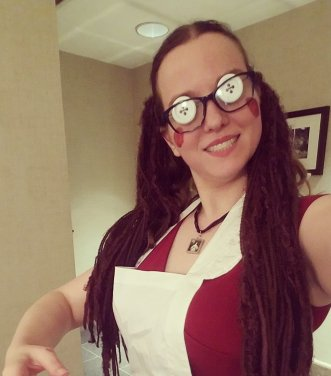 Morgan, in a red dress, covered by a white apron, dark glasses, with white button eyes. Her brown hair is in pigtails, with yarn hair-falls