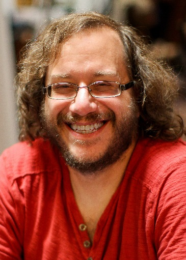 Keith DeCandido's profile picture. He's a white male with wavy shoulder-length brown hair, with a neatly trimmed beard and moustache, wearing a red shirt and rectangular glasses.