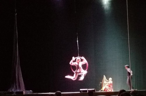 A girl on a suspended hula hoop, a man in a hat, and a lady in a red robe at a large harp on stage.