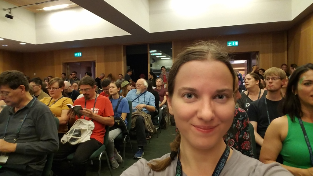 Morgan taking a selfie while sitting near the front of a room full of chairs. (She's at a writing panel at a convention)