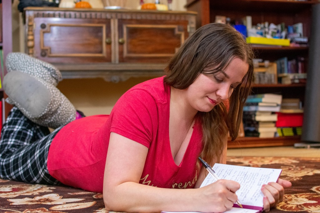Morgan, a long-haired brunette, is laying on a carpet, legs in slippers kicked up behind her, writing in a notebook.  Behind her is a table and a bookshelf.
