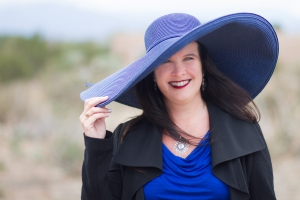 Picture of Jeffe Kennedy - a brunette white woman in a blue top and a very wide rimmed, bright blue hat.  Background is blurred, but is clearly outside. Green and rock or dirt.